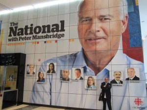 Constable Tony Vella dwarfed by Wall Portrait of CBC The National's Peter Mansbridge